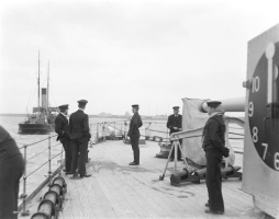 British officers on board the light cruiser HMS Caradoc watching the shore at Liepāja. December 1918. Image – Imperial War Museums
